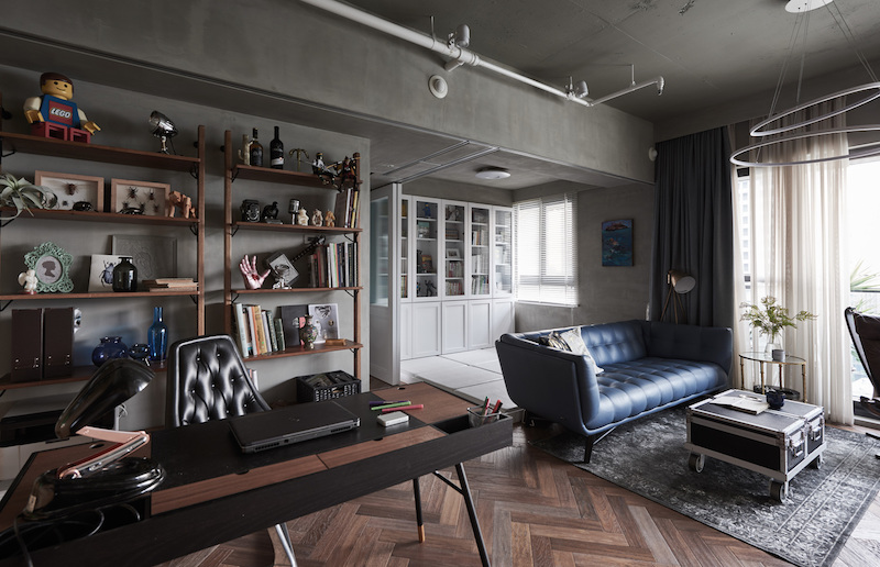 The living area also incorporates an open study with an elegant writing desk and industrial pipe shelving