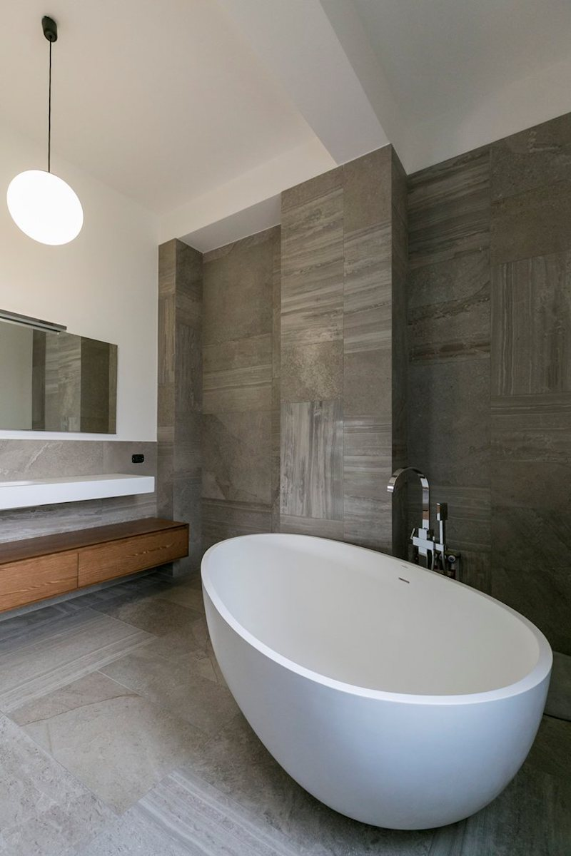 The bathrooms mix natural stone and wood elements with soft and curvaceous forms and delicate lines
