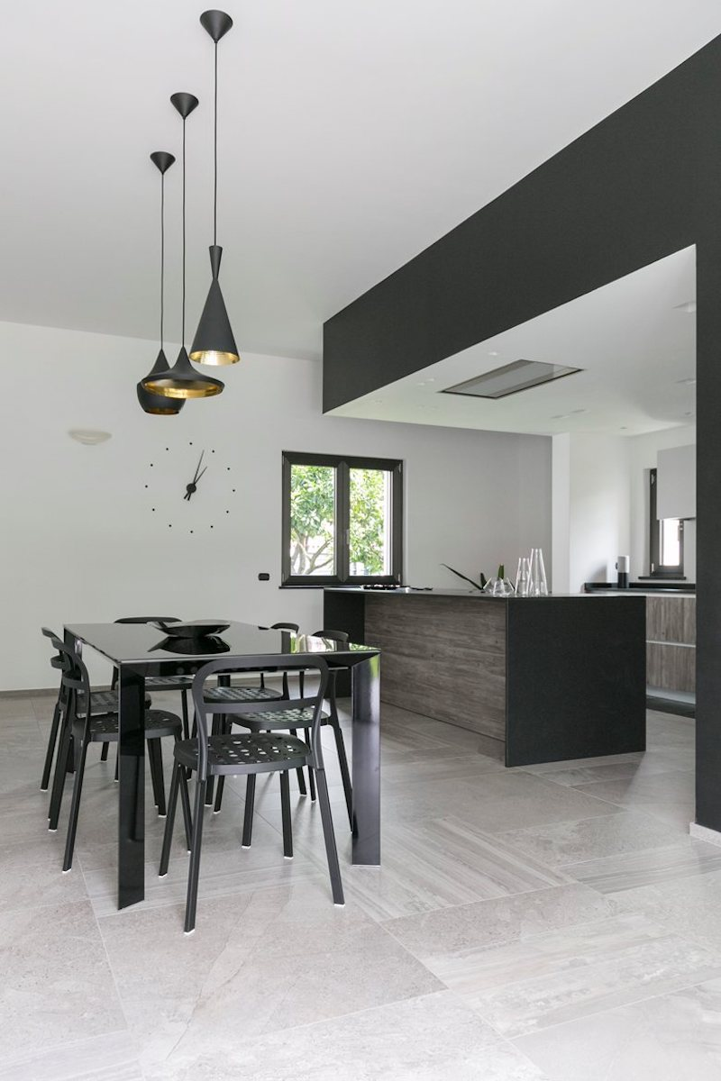 The kitchen and dining area share an open space and a minimalist design reduced to neutral colors and materials