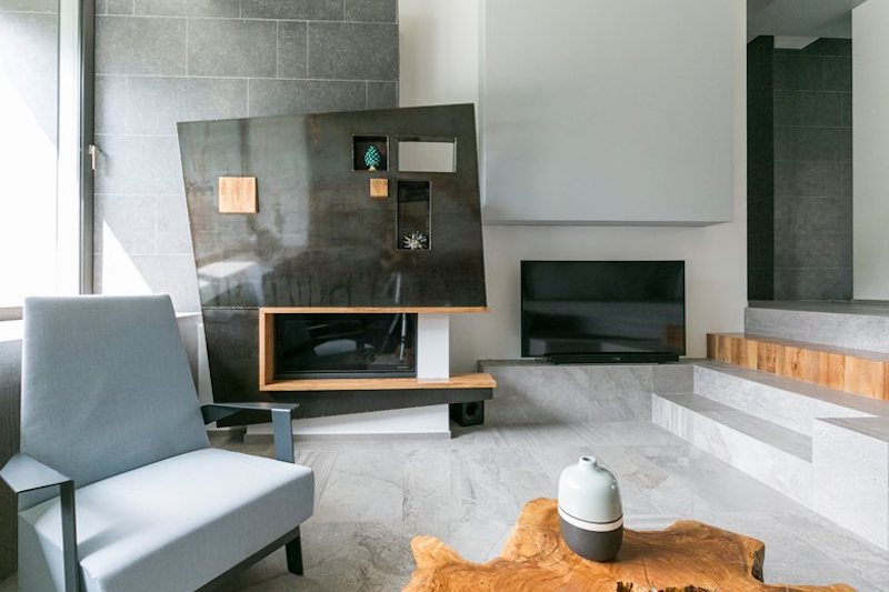 The fireplace is one of the focal points of this space thanks to its unusual geometry and its modern design