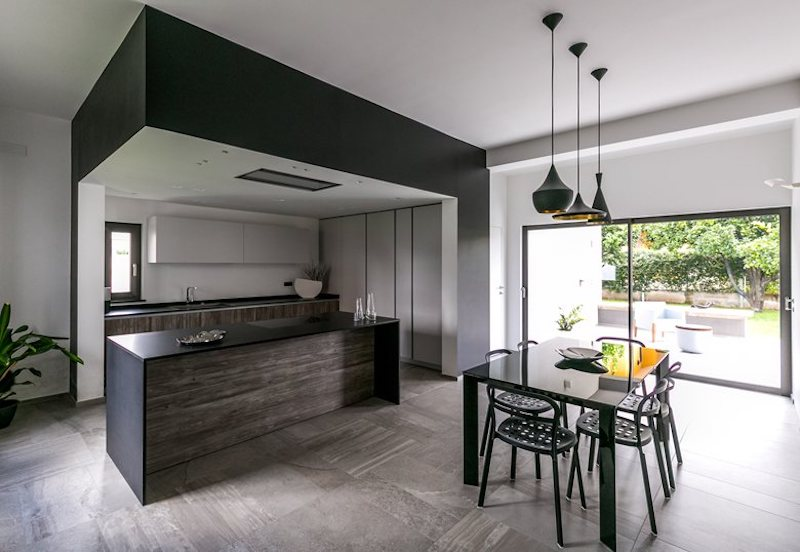 The kitchen has a compact structure and the island acts as a divider between it and the dining space