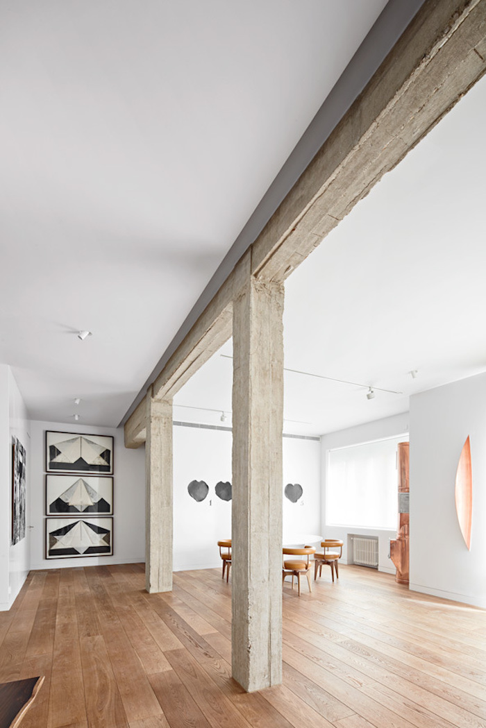 The exposed concrete beams add texture to the spaces and look nice in contrast with the oak flooring