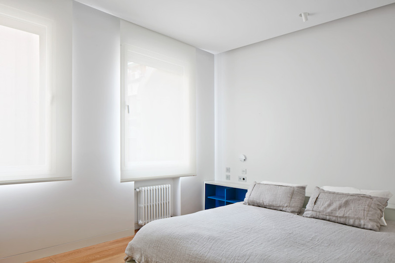 The master bedroom features the same minimalist window treatments as the living area