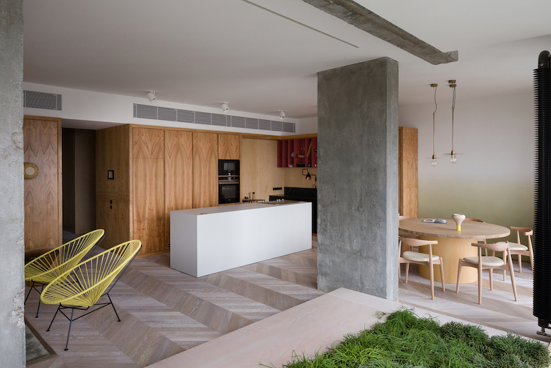 The palette of materials used throughout the apartment includes two different types of wood and concrete