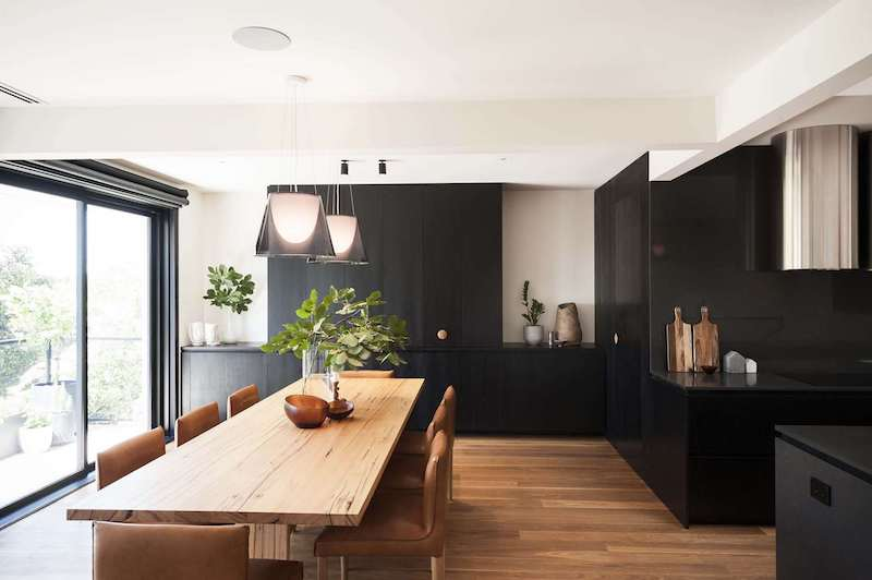 The adjacent dining area introduces warm wood accents which balance out the matte black kitchen decor