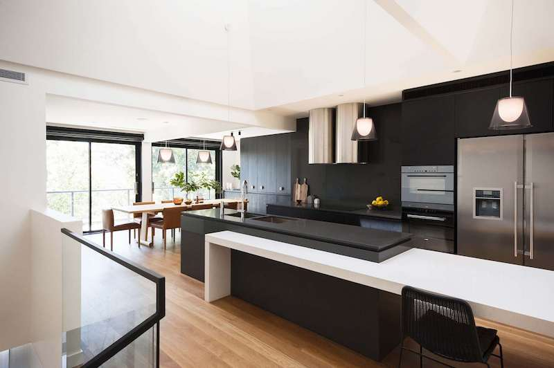 The kitchen is large and open and almost entirely black with stainless steel appliances