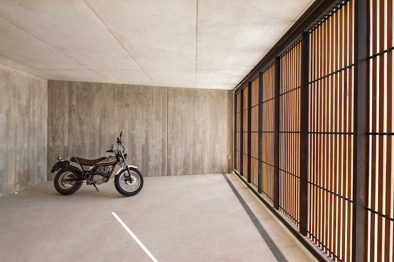 The lower section of the house contains the lobby, the service area and this minimalist garage