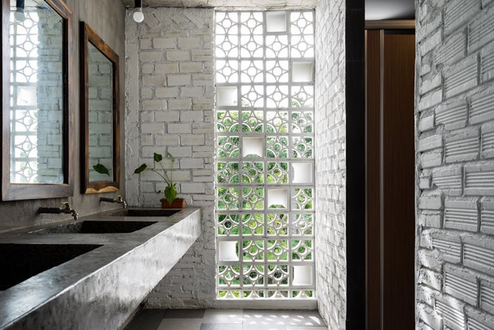 The bathrooms are shared spaces too, featuring multiple sinks and mirrors and these charming brick walls