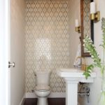 Powder room with a small design and gold accents