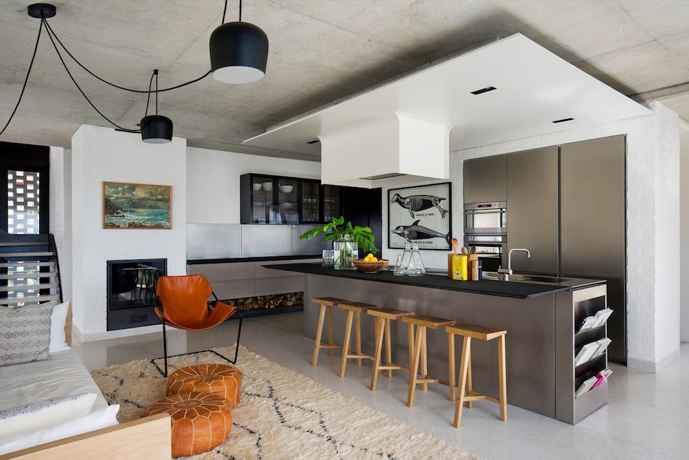 The minimalist and clean lines of the kitchen are complemented by warm and rich textures used throughout the living area