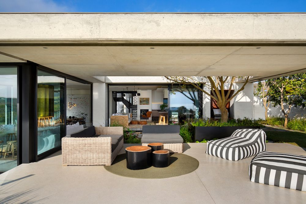 The simplicity of the materials and of the color palette is extended in the outdoor lounge area as well