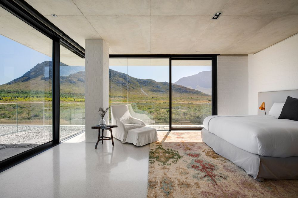 Large panorama windows and sliding glass doors lead out onto open terraces with transparent guardrails