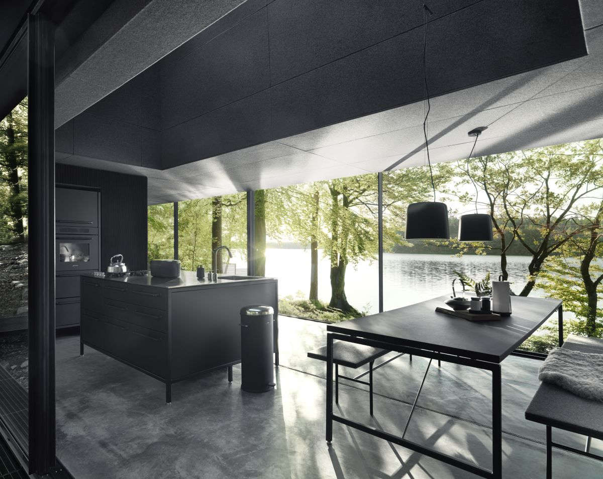 The kitchen, dining space and living area are all part of an open floor plan with glazed walls and concrete flooring