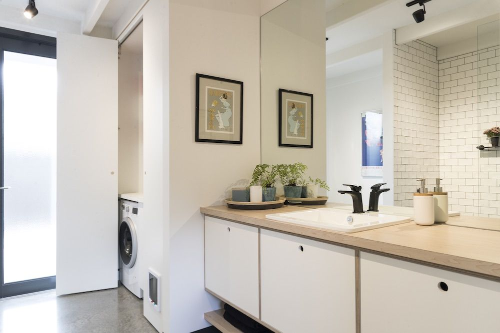 The main bathroom also functions as a laundry area, having a separate section specifically designed for this purpose