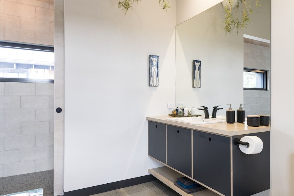 Large wall mirrors and wall-mounted vanities help give the bathrooms an open and spacious feel
