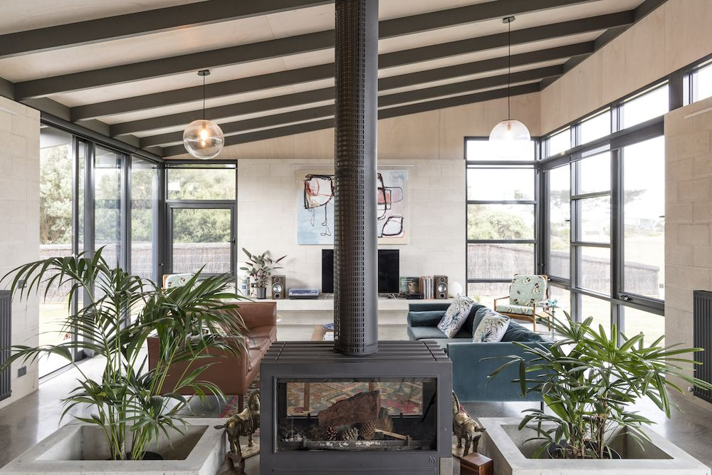 The exposed beams on the ceiling and the fireplace create a sense of warmth and comfort in the living area
