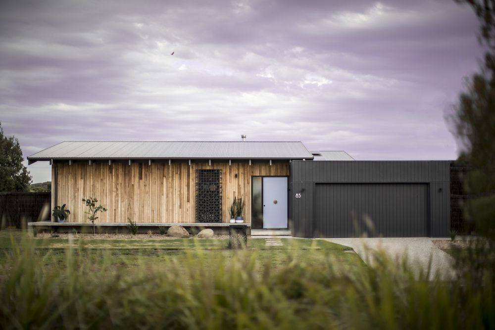 The house is clad in ash wood on the outside and has a garage with a black shell which contrasts with the living spaces
