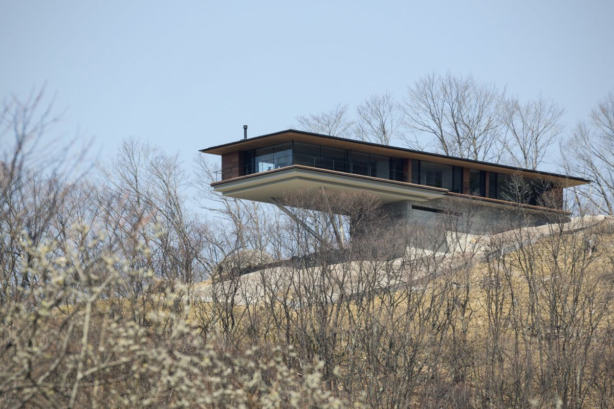 The house manages to blend into the landscape and to let the outdoors in while also standing out and looking imposing
