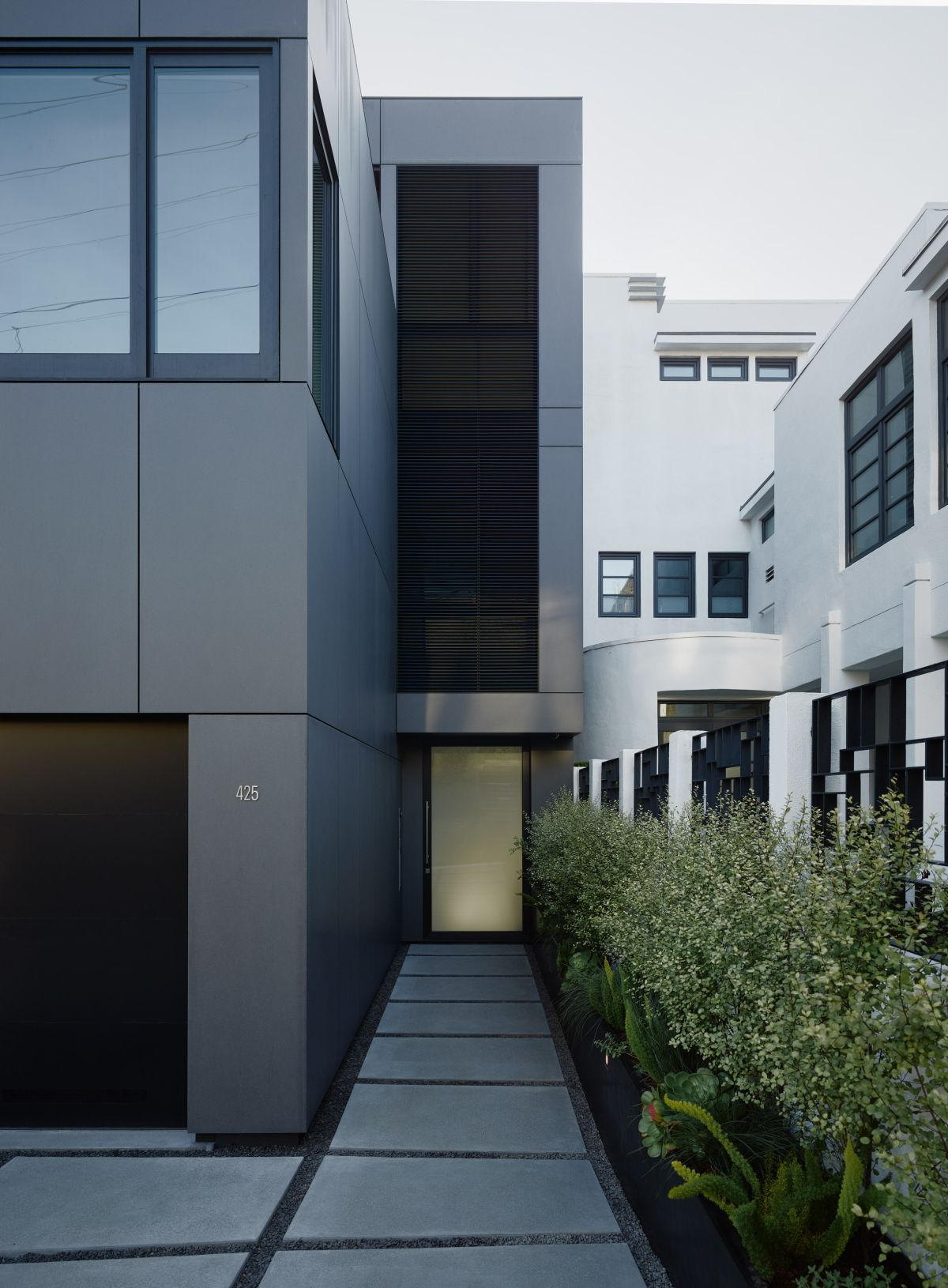 The house sits on a sloping site with very little room between it and the neighboring properties. This proximity inspired the architects to design a dark facade