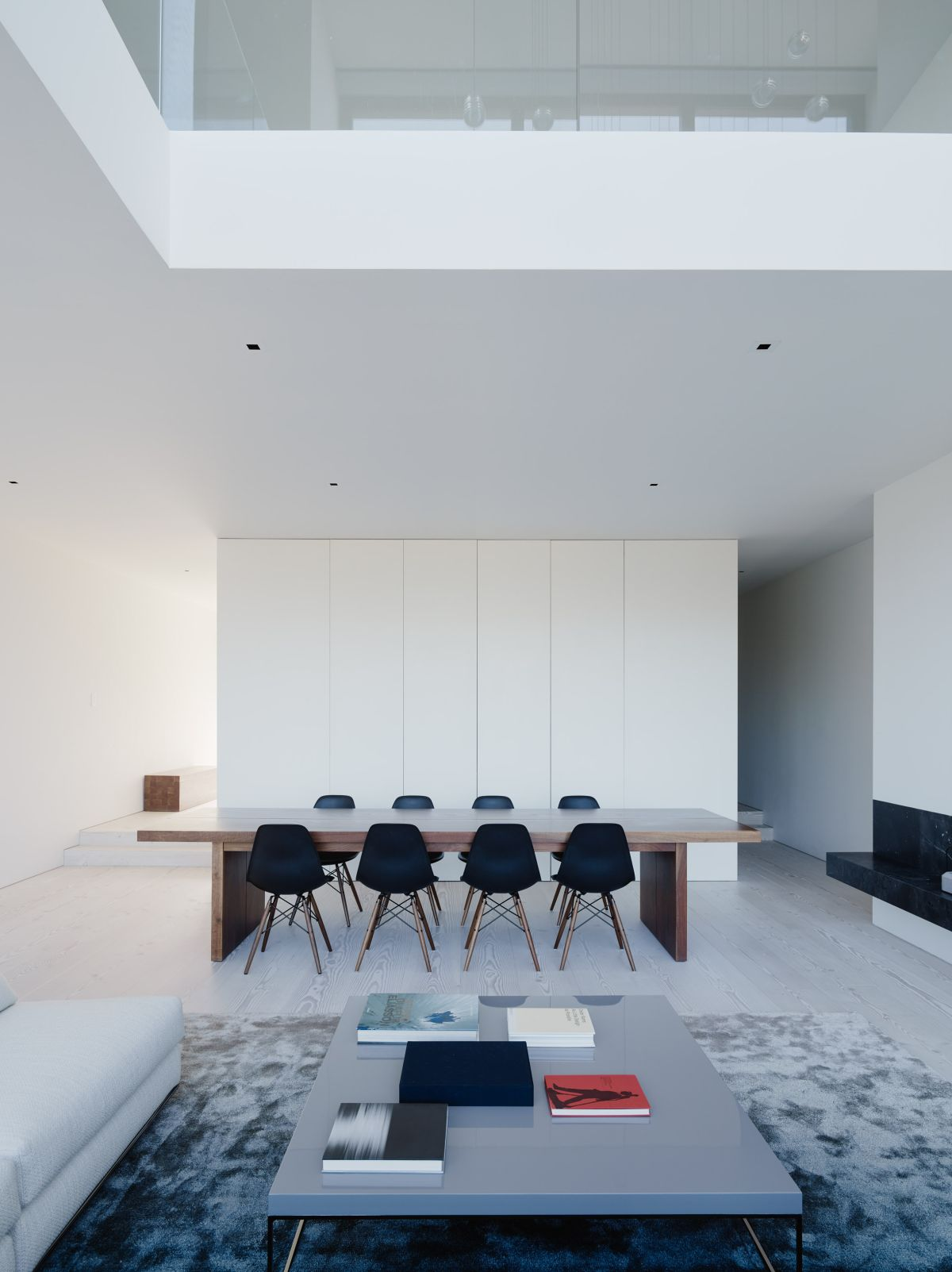 The interior design is minimalist and features an all-white palette, the walls representing blank canvases for the furniture to contrast with