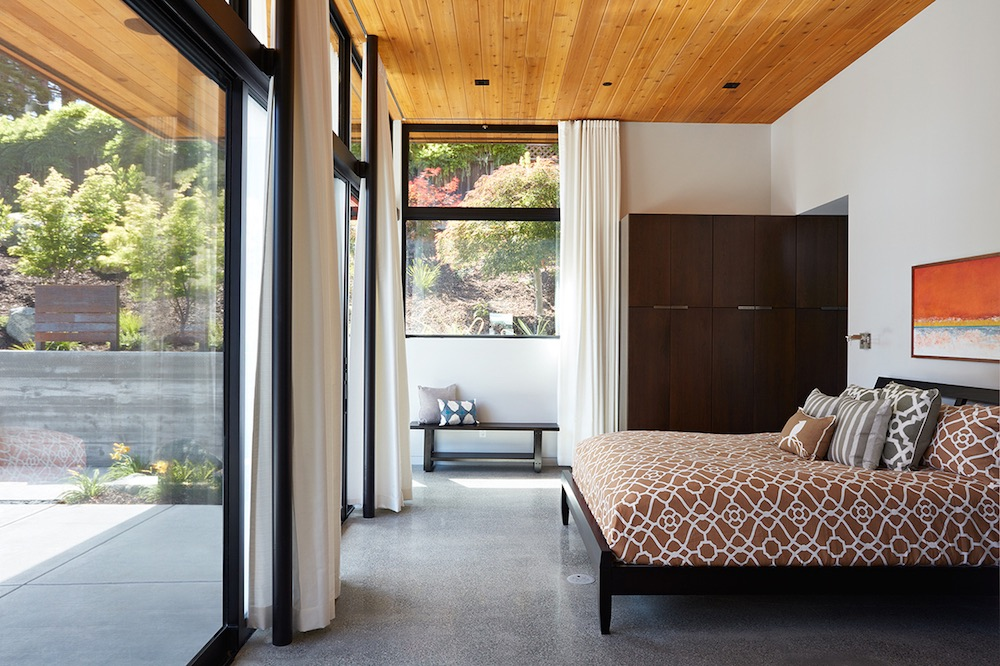 A simple bench sits by the windows on the side wall of the bedroom, offering a cozy seating area