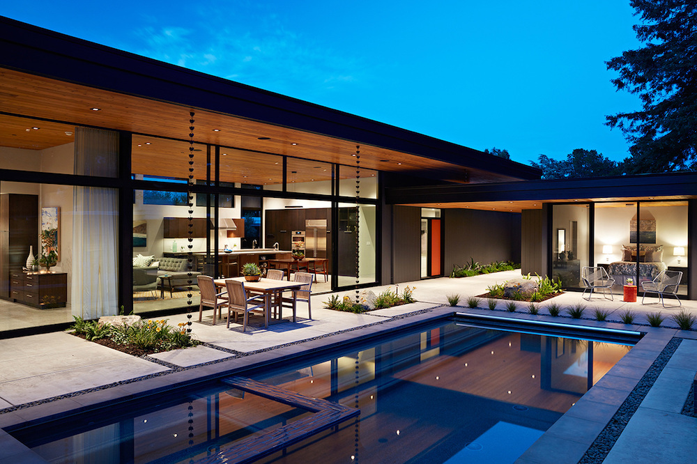 The house has an L-shaped floor plan with interior zones that open up to the decks and the pool