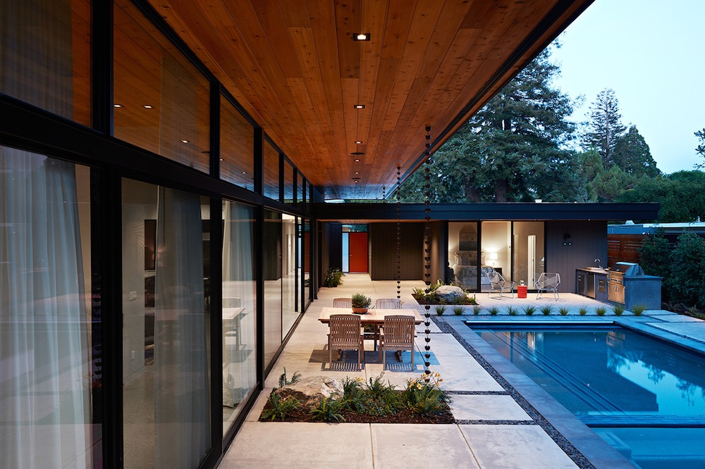 The overhanging roof extends outdoors and offers shelter for the dining space and poolside area