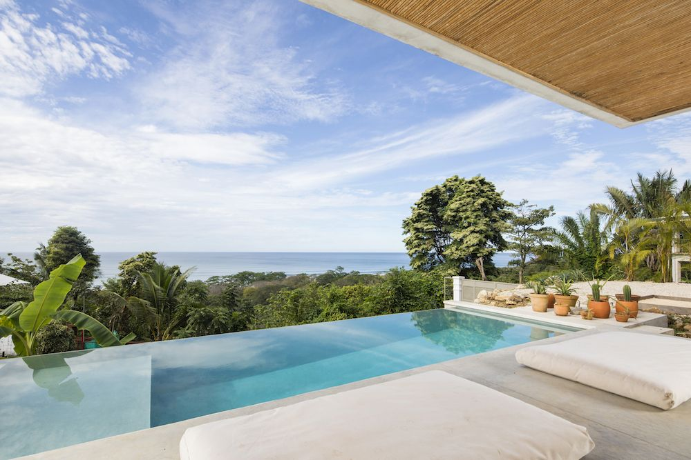 The infinity edge pool overlooks the tree canopies and the ocean just a short distance away