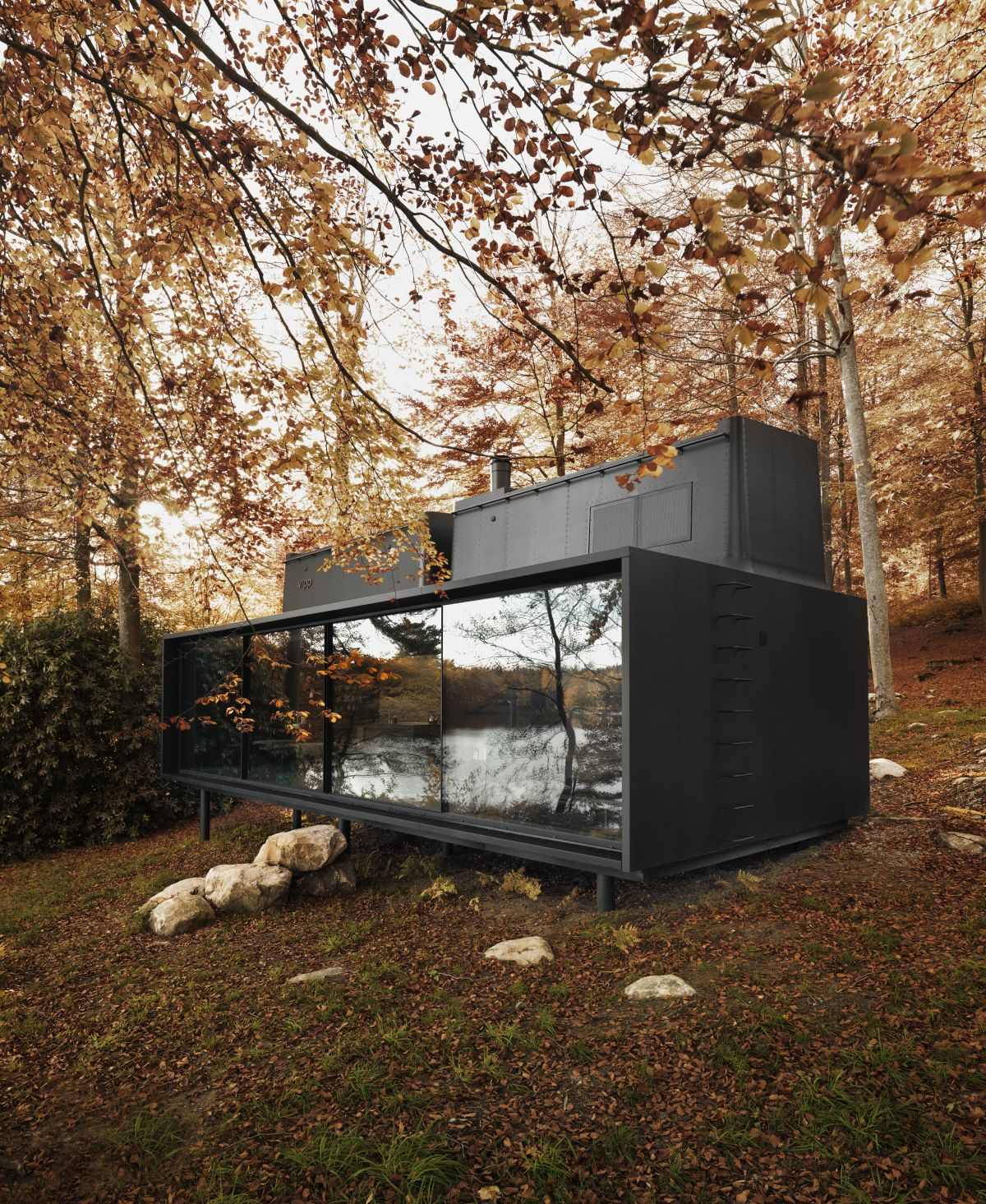 The exterior of the cabin is minimalist and made of metal, featuring a dark gray color which contrasts which just about any environment