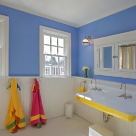 Bathroom with yellow accent through accessories and white beadboard