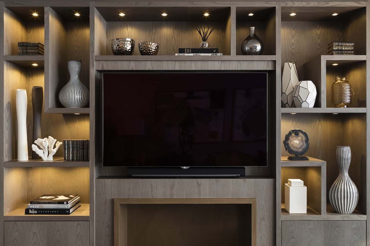 LIghted shelving counteracts the dark television screen.