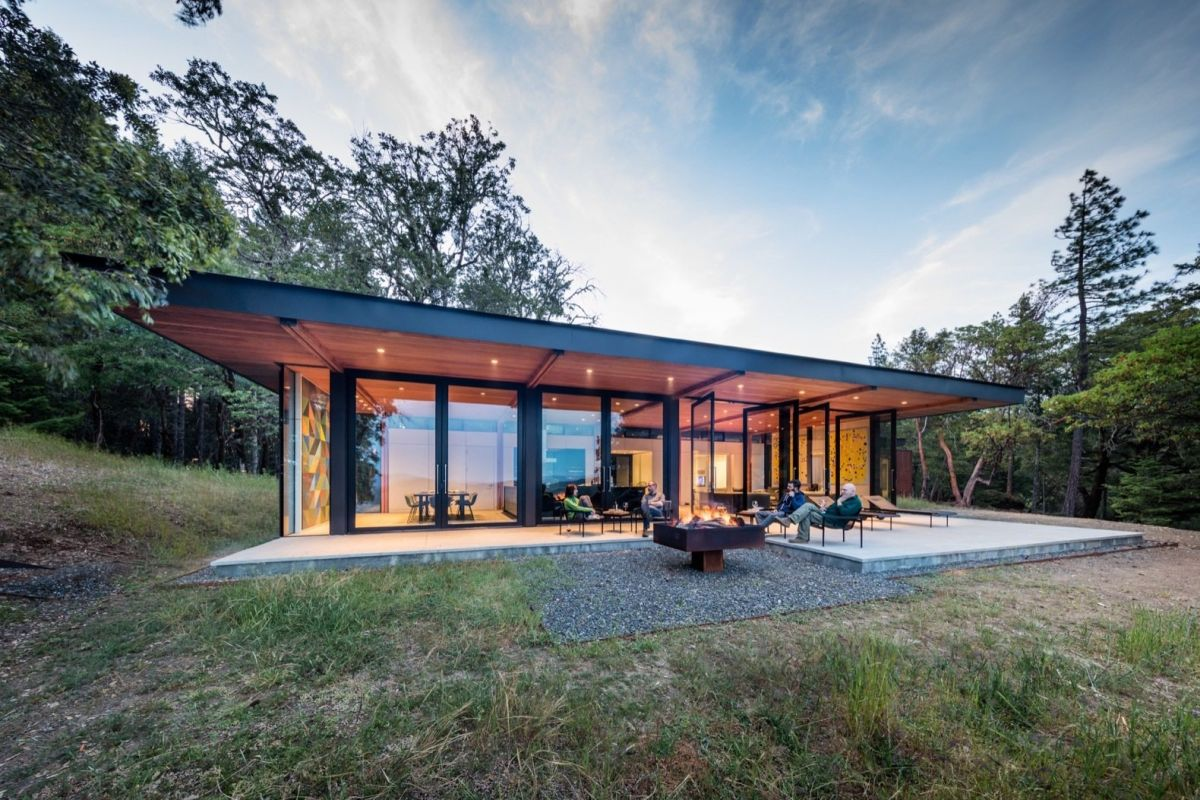 Low slung and minimal, the house blends with the wooded surroundings.