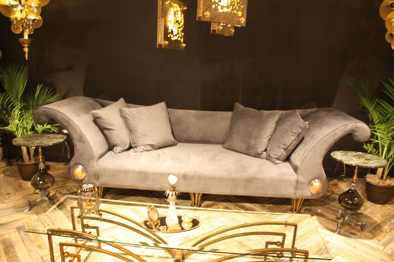 Nick Alain's sofa features boldly curving arms while the table base has legs typical of this style.