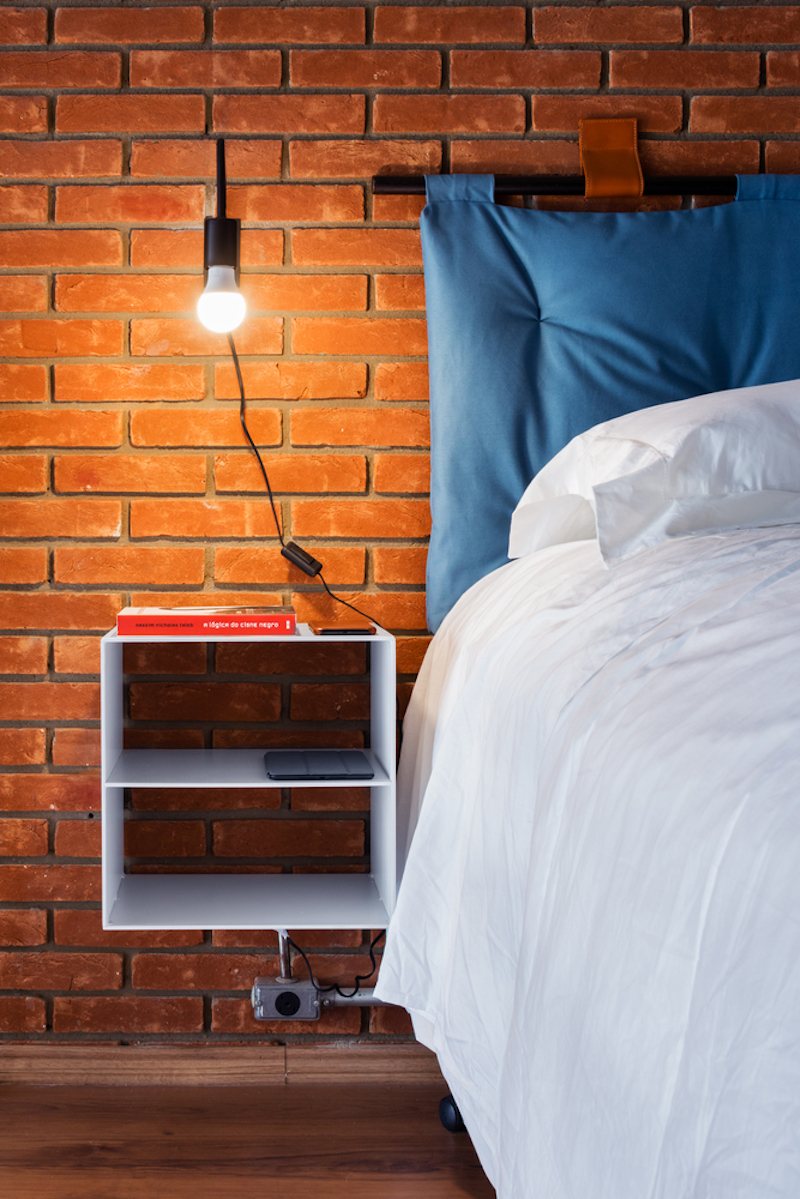 Simple cord lighting highlights the texture and color of the brick wall as well as the sleek wall-mounted nightstands