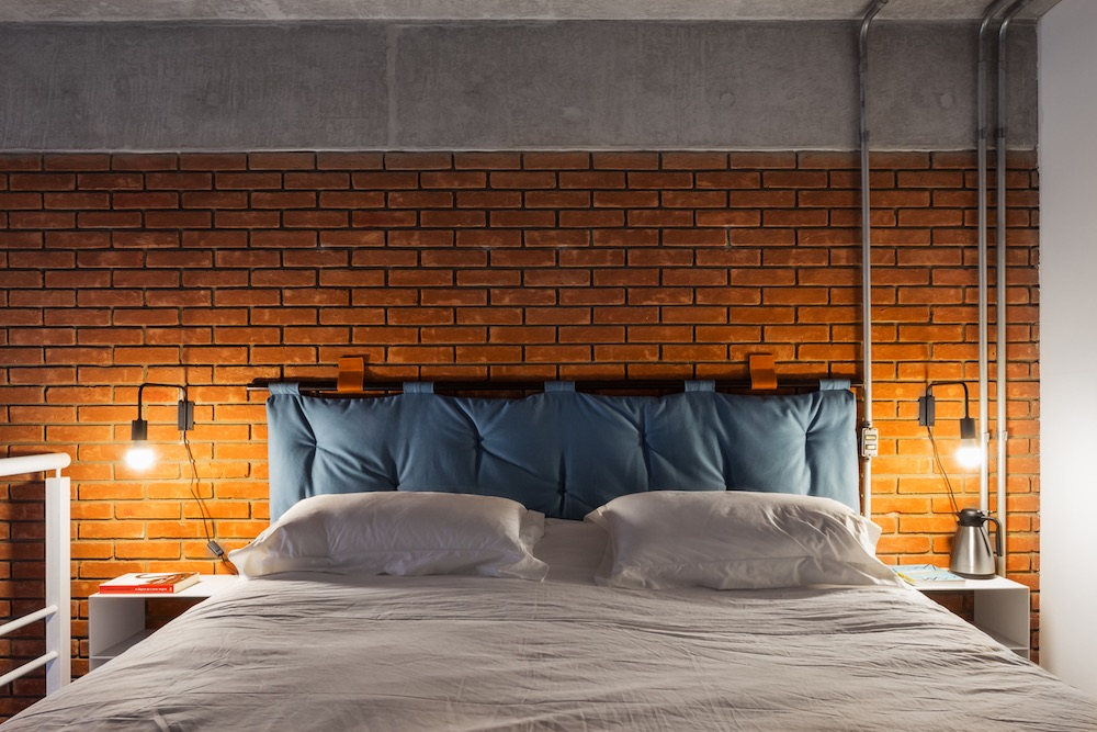 The loft bed has this cool headboard which is in tone with the rustic-industrial vibe of the space