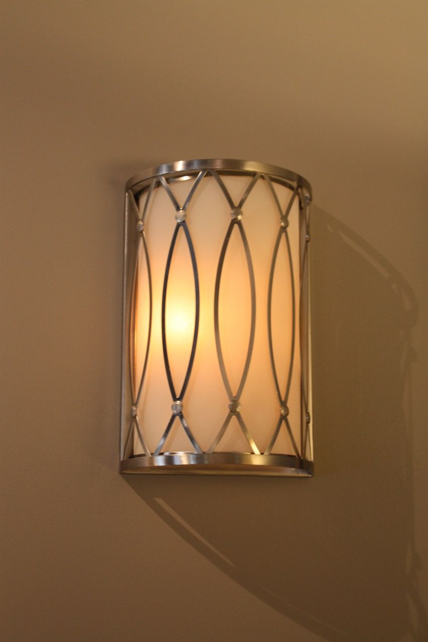 This basic wall sconce features a curved motif typical of the era.