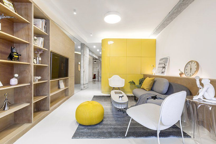 The yellow of the kitchen box is complemented by light wood accents, grays and crisp white surfaces