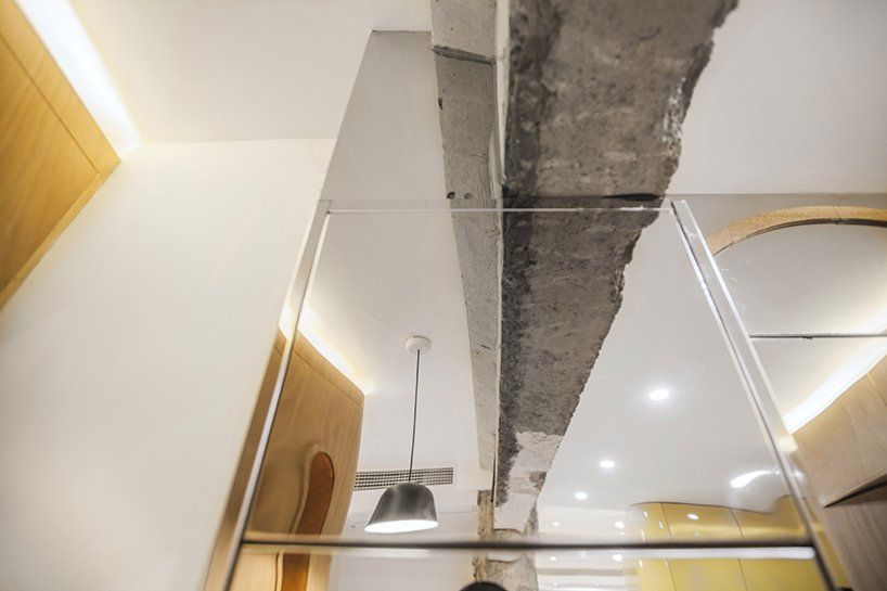 The mirrors reflect the space and some of its coolest features, like this rugged, exposed concrete beam