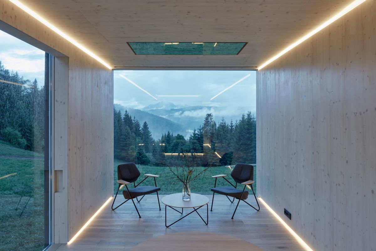 The interior of the cabin is organized into several zones. This is a dining space with a gorgeous view and accent lighting