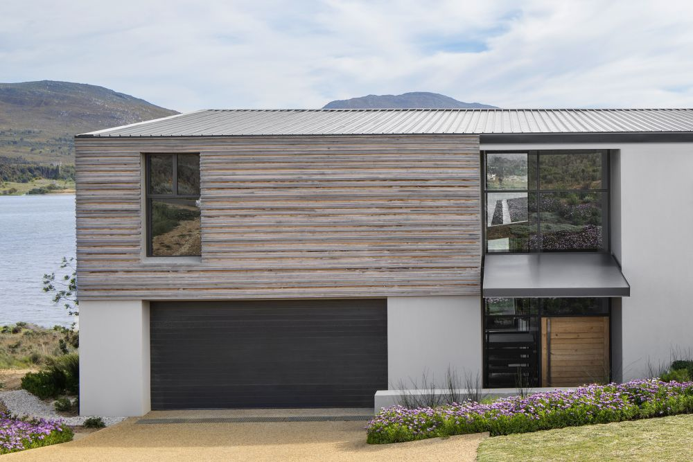 The flat corrugated aluminum roof gives the house a sleek and modern appearance