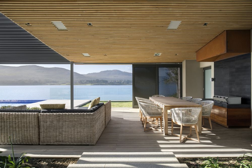 Large full-height windows open up the interior living spaces to the views of the water and the distant mountains