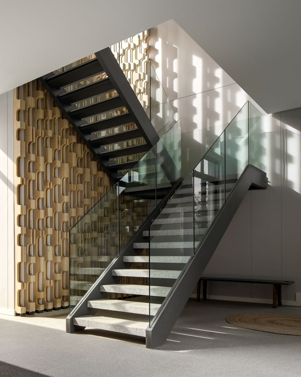 The staircase which connects the two floors has glass railings and is complemented by a decorative wall