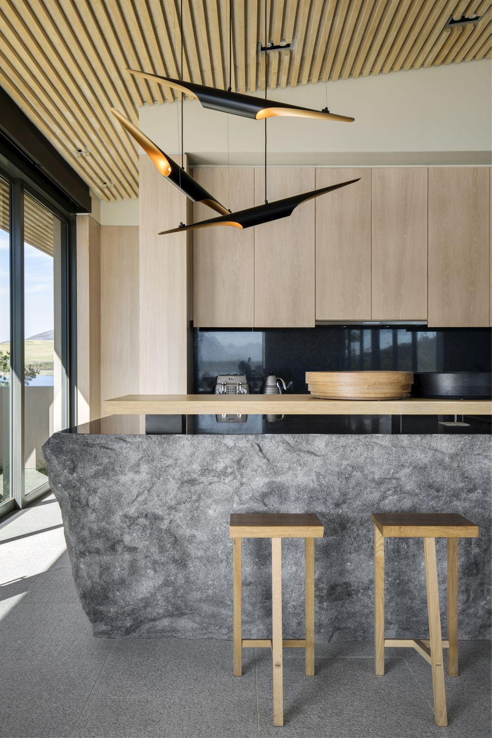 The sculptural hanging lights complement the kitchen's decor and furnishings in a very chic way