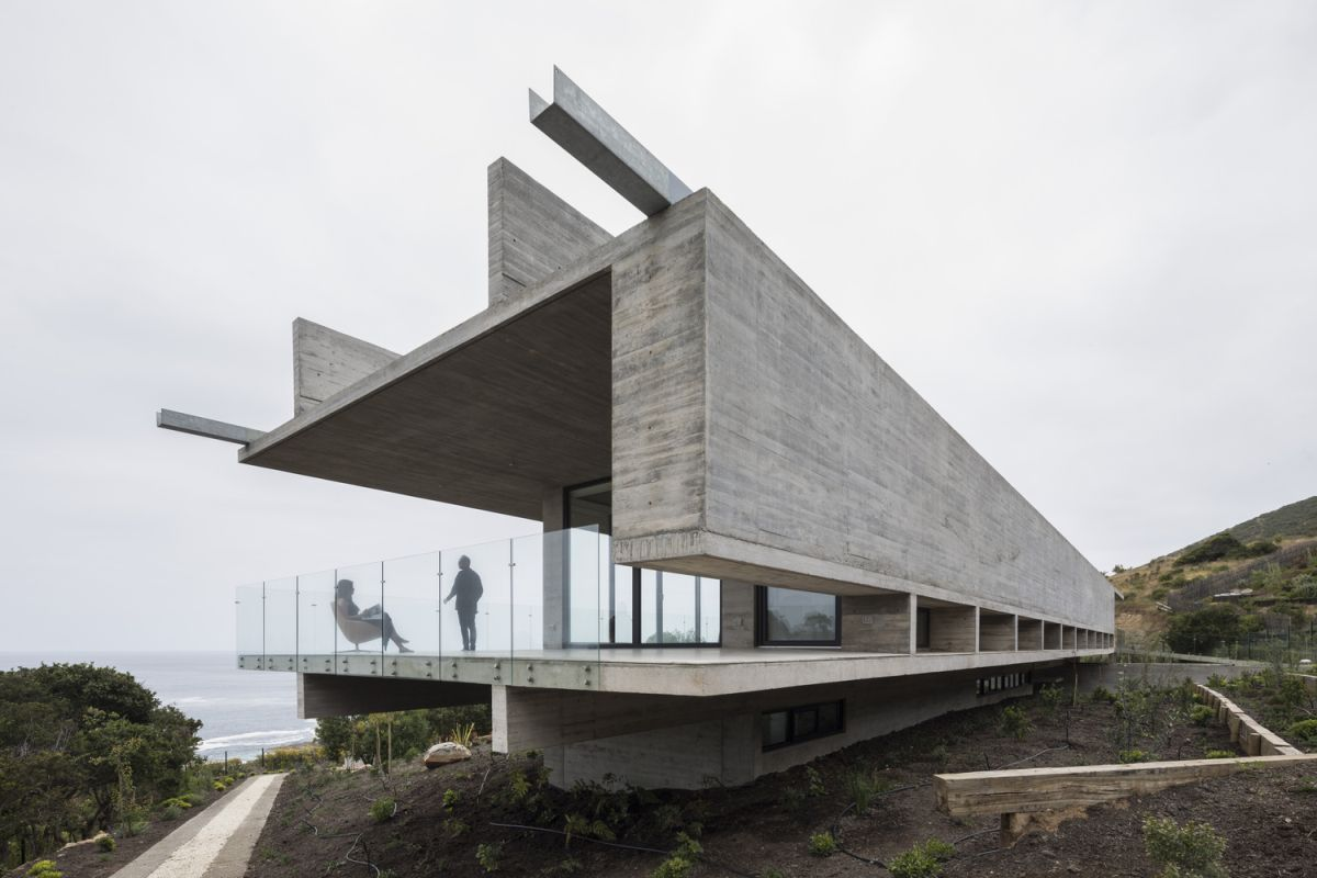 A large covered terrace with glass railings stands at each end of this long concrete house