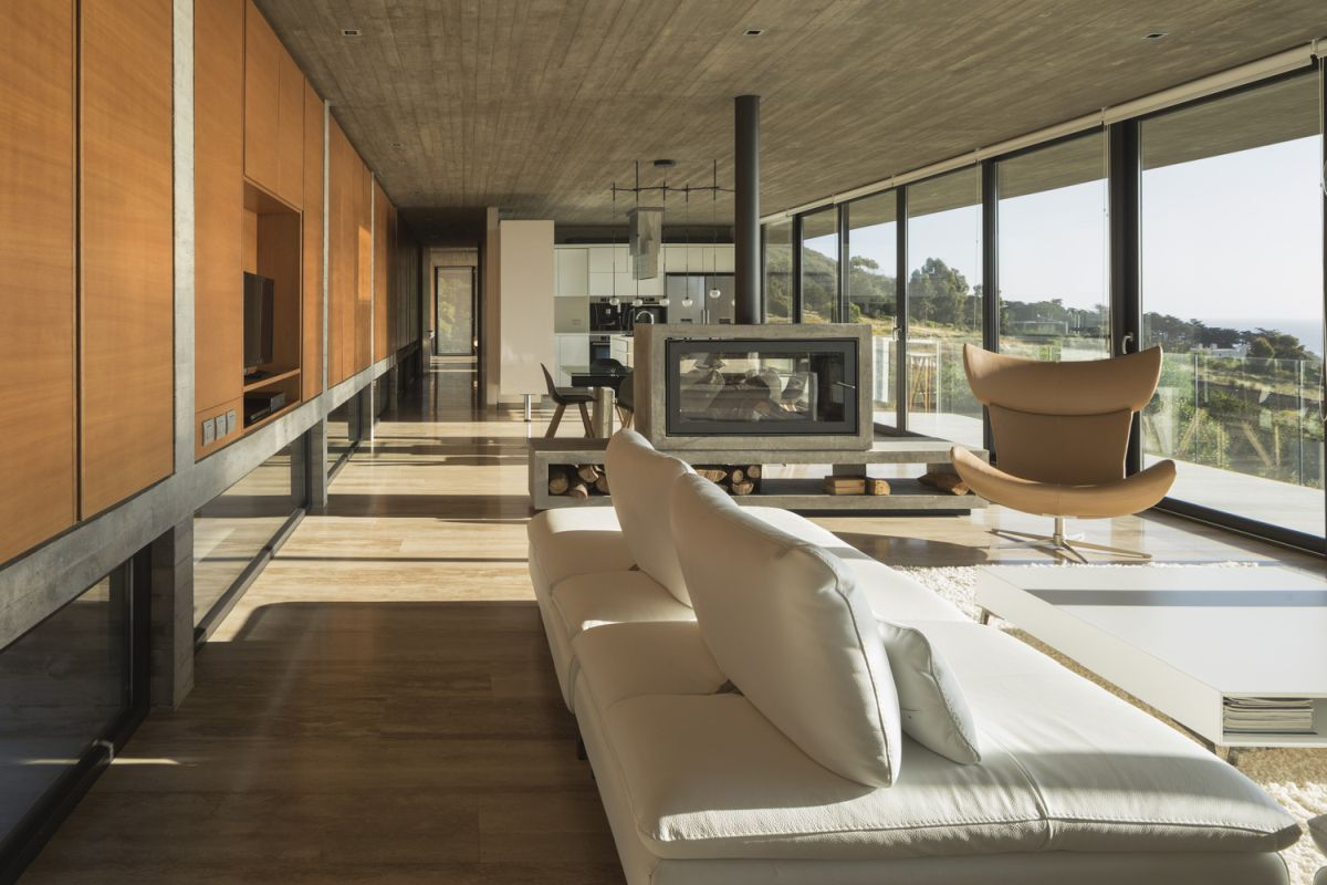 The interior is simple, bright and airy, featuring a large social zone with full-height windows and sliding glass doors