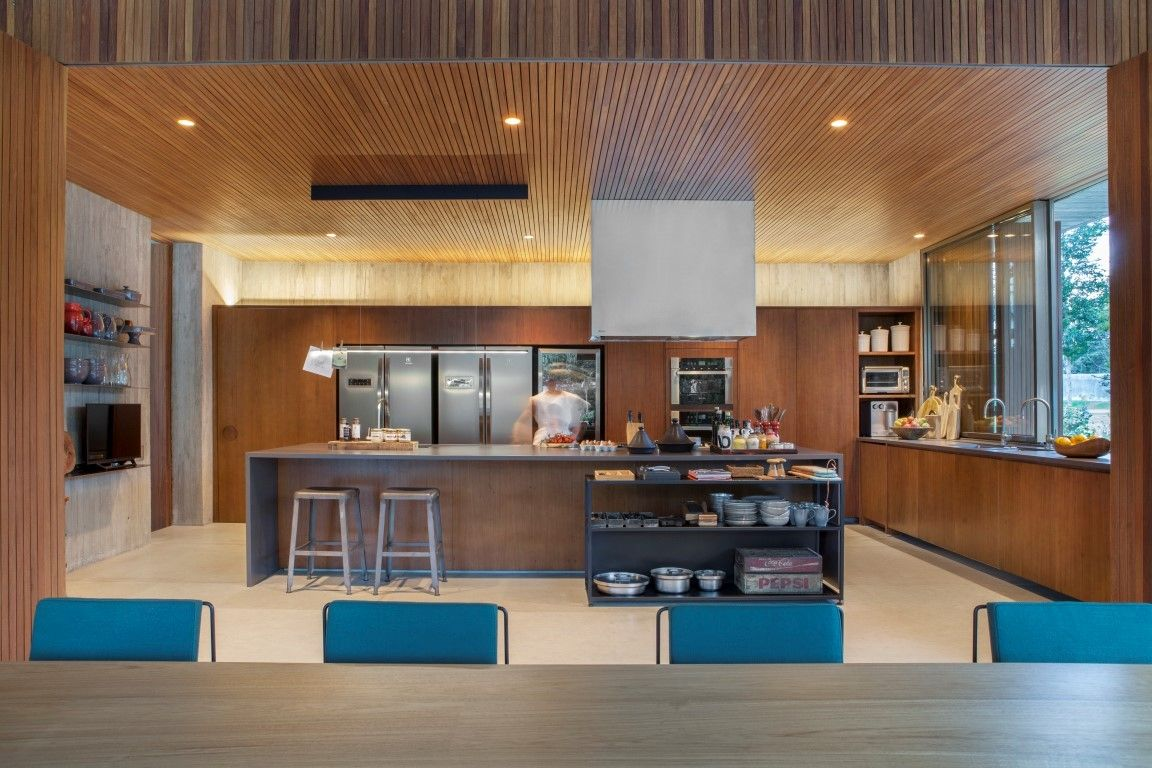 An open gourmet kitchen with soothing warm lighting is placed at one end of the open plan living zone