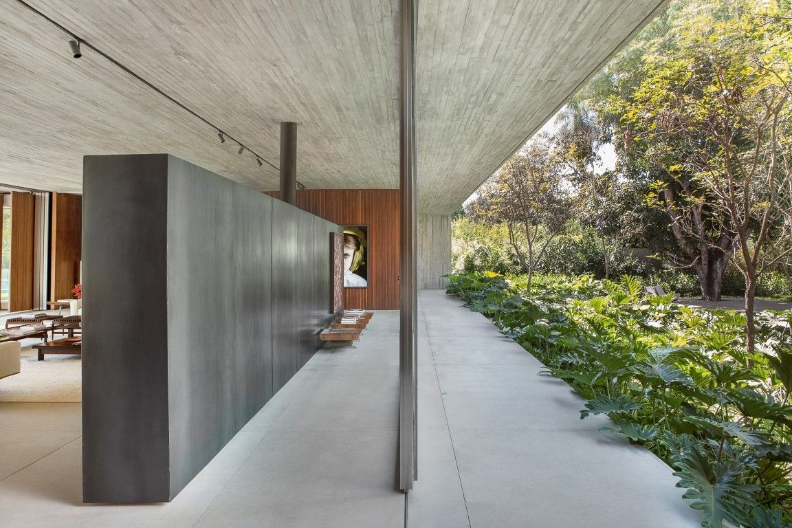 The floor and ceiling extend seamlessly to form a frame around the living spaces which acts as a buffer between the house and the garden