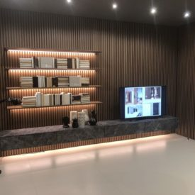 Modern wall living room design with floating shelves and LED light