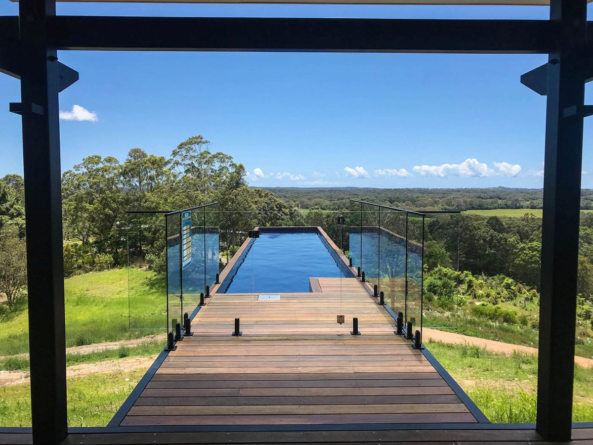 Glass railings frame the transition area between the deck and the pool, ensuring safety and expansive views