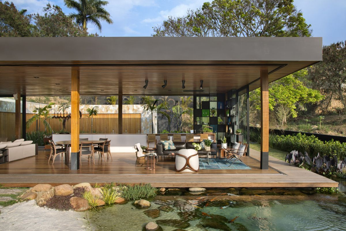 The living space is framed by a narrow wooden deck which appears to be floating above water